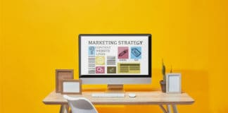 Computer with marketing strategy website on screen at wooden table